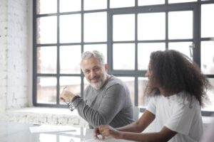 cheerful senior gray haired mentor supporting young black colleague in office